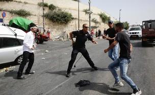 שוטרים מגנים באקדח שלוף על הפצוע בעת ניסיון הלינץ' (צילום: שלו שלום, TPS)