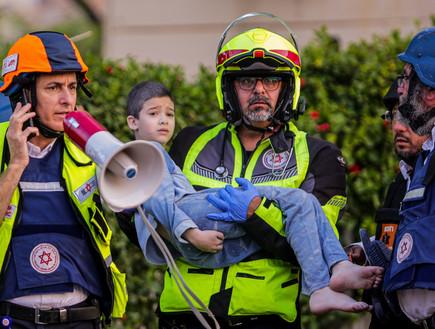 איתן וינשטוק בן השמונה מפונה על ידי חובש מבניין באשקלון (צילום: אדי ישראל, פלאש 90)