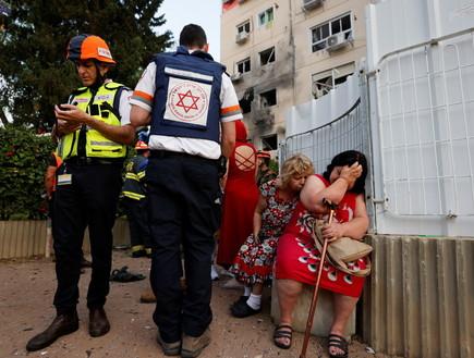 חובשים ישראלים עומדים ליד נשים שבניין מגוריהן נפגע מרקטה באשקלון (צילום: רויטרס)