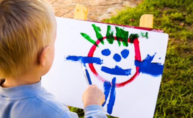ילד מצייר ציור עם מכחול מצולם מגבו (צילום: RapidEye, Istock)