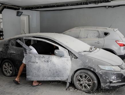 רכב מאובק בחניון ביניין שנפגע מרקטה באשקלון (צילום: רויטרס)