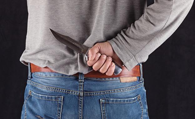 גבר מחזיק סכין מאחורי הגב (אילוסטרציה: Shutterstock)