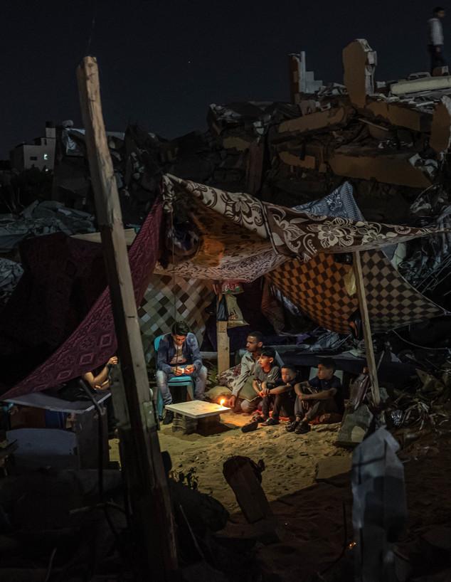 פלסטינים יושבים באוהל על הריסות בניין שהופצץ על ידי חיל האוויר (צילום: Fatima Shbair, Getty Images)