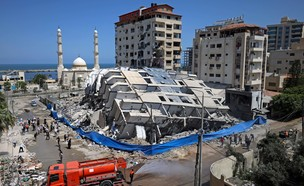 מתנדבים מנקים הריסות של בניין שהופצץ בשכונת רימאל בעזה (צילום: MOHAMMED ABED, AFP)