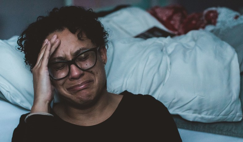 אישה בוכה ליד מיטה (אילוסטרציה: Claudia wolff, unsplash)