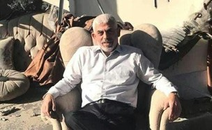 מנהיג חמאס ברצועת עזה, יחיא סינוואר, על כורסה במשרד ההרוס