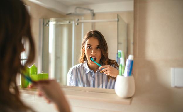 אישה מצחצחת שיניים (צילום: By Dafna A.meron, shutterstock)