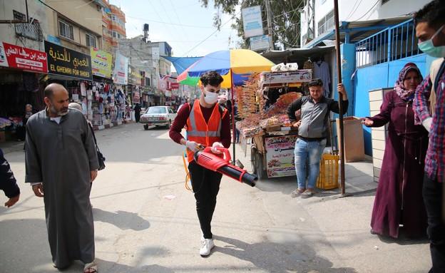 עובד פלסטיני מחטא קניון בעזה מנגיף הקורונה (צילום: אלי אחמד , פלאש 90)