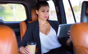 אישה יושבת במכונית ומסתכלת על טאבלט בזמן שתיית קפה (אילוסטרציה: Q-stock, shutterstock)