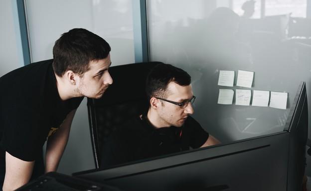 שני גברים מול מחשב במשרד (צילום: Maxim Tolchinskiy   @shaikhulud, unsplash)