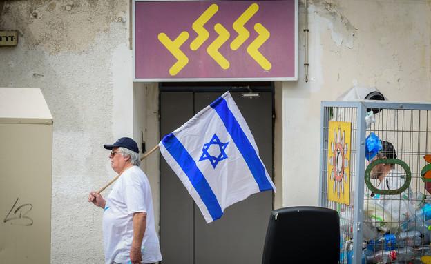 """מפגין עם דגל ישראל מול משרדי גלגל""""צ (צילום: אבשלום ששוני, פלאש 90)"""