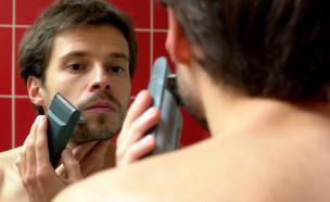 גבר מתגלח במכונה מול מראה (צילום: אור גץ, istockphoto)