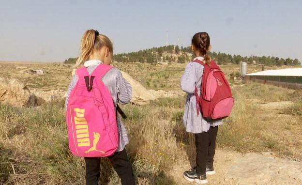 """ילדות מהכפר טובא מחכות לאבטחת צה""""ל בדרך לבית ספר (צילום: חדשות 12)"""