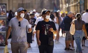 אנשים הולכים ברחוב עם מסכות (צילום: אוליבר פיסוטי, פלאש 90)