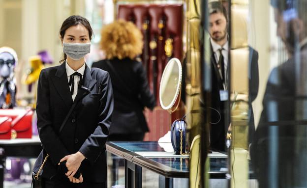 עובדת בחנות למוצרי יוקרה בסידני לובשת מסיכה (צילום: Jenny Evans, Getty Images)