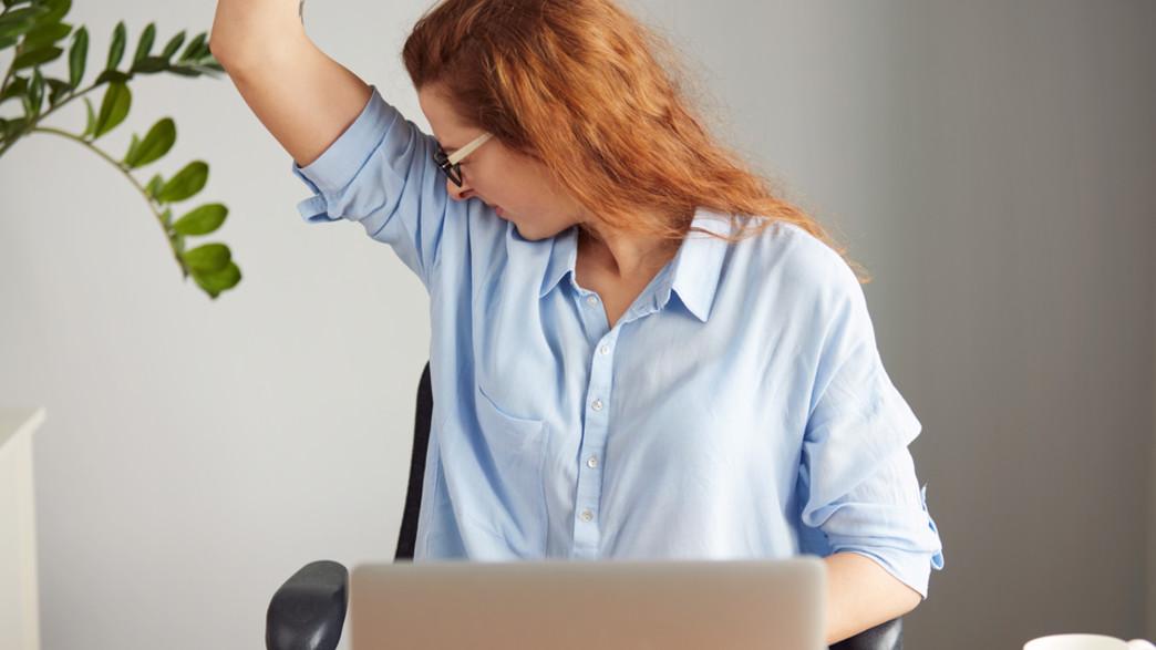 אישה מזיעה במשרד (אילוסטרציה: Shutterstock)