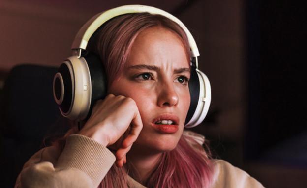 צעירה מודאגת עם אזניות (צילום: Dean Drobot)