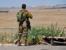 """חייל צה""""ל מסתכל לעבר סוריה סמוך לגבול (צילום: באסל עווידאת, פלאש 90)"""