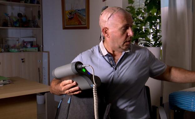 אדי פלג כשעליו המכשיר לטיפול בסרטן  (צילום: חדשות 12)