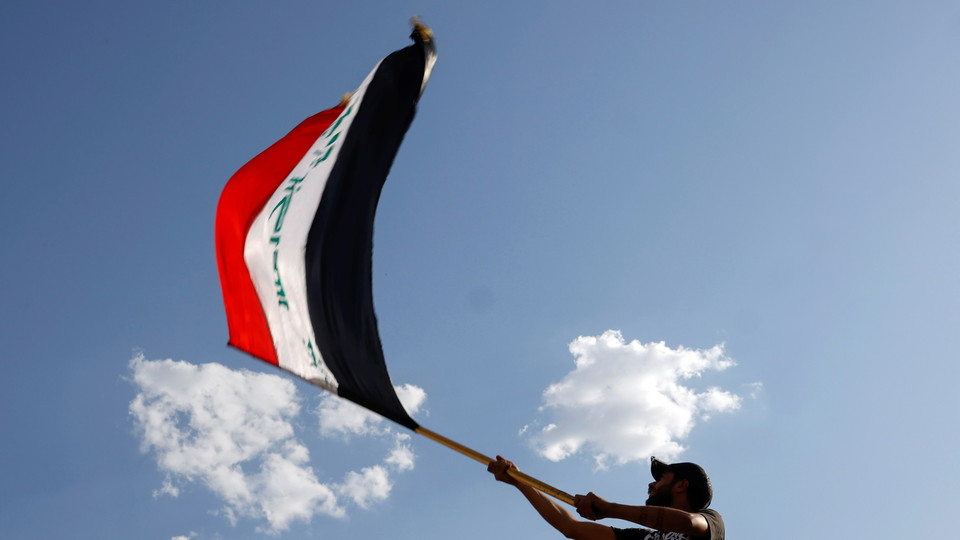 דגל עירק מונף בהפגנה (צילום: רויטרס)