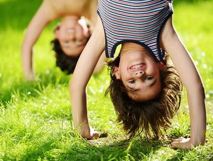ילדים מחייכים עומדים על הידיים (צילום: Zurijeta, Shutterstock)