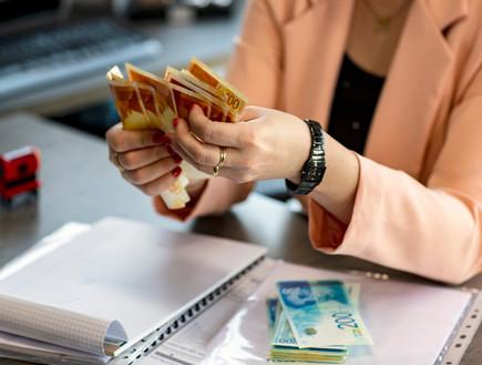 אישה מחזיקה שטרות  (אילוסטרציה: Lady_Luck, shutterstock)